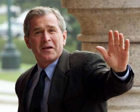 Bush raises his hand in a futile attempt to block the picture before seeing it.